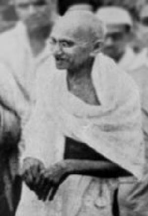 Mohandas Karamchand Gandhi smling at crowd.